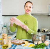 Woman cooking filleted fish — Stock Photo