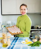 Smiling woman cooking filleted fish — Stock Photo