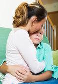 Woman comforting crying teenager son — Stock Photo