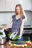 Blonde woman cooking lubina fish — Stock Photo