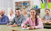 Adult students writing in classroom — Stock Photo