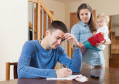 Depressed woman with baby and husband — Stock Photo