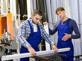 Workers cutting window profiles — Stock Photo