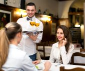 Smiling waiter serving guests — Stock Photo