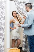 Boy waiting for girl trying on clothes — Stock Photo