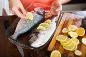 Housewife putting  lemon in fish — Stock Photo