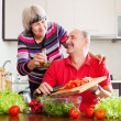 Happy  elderly couple cooking with tomatoes — Stock Photo #75034707