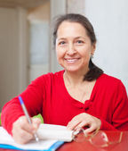 Gladful  woman fills in documents — Stock Photo