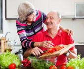 Happy loving elderly couple in kitchen — Stock Photo