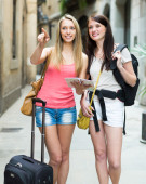 Girls with luggage reading map — Stock Photo