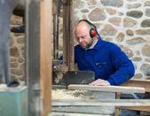 Homem que trabalha em uma máquina na oficina — Fotografia Stock