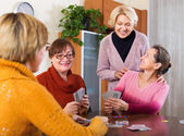 Pensioners having fun with cards — Stock Photo