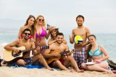 Friends with guitar at beach — Stock Photo