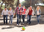 Happy friends chasing ball outdoors — Stock Photo
