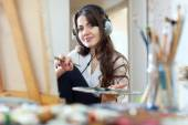 Girl in headphones  paints with oil colors — Stock Photo