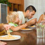 Family of four eating spaghetti — Stock Photo #75060279