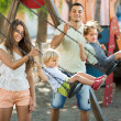 Parents with kids at swings — Stock Photo #75060343