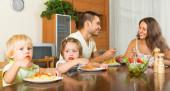 Family of four eating spaghetti — Stock Photo