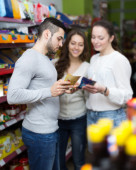 Customers  near shelves with canned goods — Stock Photo