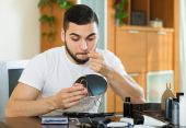 Man plucking hair from his nose with pliers — Stock Photo