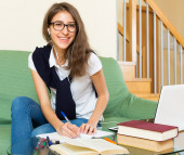Young girl using laptop at home — Stock Photo