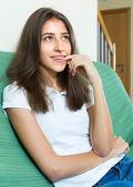 Girl sitting at sofa and biting nails — Stock Photo