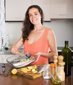 Woman cooking fishes at kitchen — Stock Photo