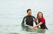 Couple in wetsuits with surf board — Stock Photo