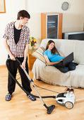 Homme, nettoyage tandis que femme couchée avec ordinateur portable — Photo