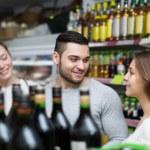 Shoppers choosing bottle of wine — Stock Photo #77491020