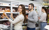 Customers near fridge with meat products — Stock Photo