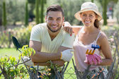 Couple in gloves with horticultural sundry — Stock Photo