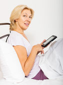 Cheerful  middle-aged girl with ereader — Stock Photo