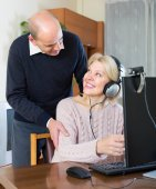 Senior couple using PC at home — Stock Photo