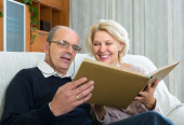 Senior spouses with picture album indoor — Stock Photo