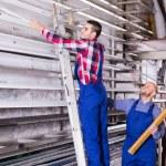 Two workers choosing PVC window profile — Stock Photo #79692298