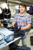 Male chooses jeans at clothing store — Stock Photo