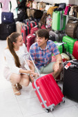 Male and female chooses suitcase — Stock Photo