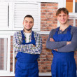 Two young workmen inspecting windows — Stock Photo #79703366