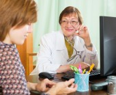 Elderly doctor communicates with patient — Stock Photo