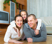Family smiling at the floor — Stock Photo