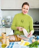 Attractive woman cooking fish — Stock Photo