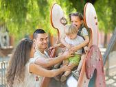 Slayt üzerindeki çocuklara yardım ebeveyn gülümseyen — Stok fotoğraf