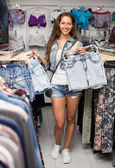 Girl selecting shorts in clothing store — Stock Photo