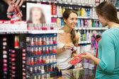 Girl choosing nail polish at store — Stock Photo