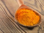Turmeric powder in a wooden spoon. — Stock Photo