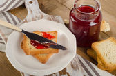 Strawberry jam topping a slice of toast — Stock Photo