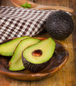 Fresh avocados on  wooden board .  — Stock Photo