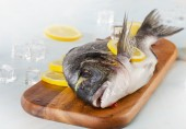 Raw fish with lemon — Stock Photo