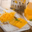 Grated Cheddar Cheese on  a wooden Board — Stock Photo #76842827